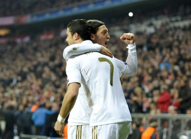 Real Madrid's Cristiano Ronaldo congratulates team mate Mesut Ozil on finding a spare jersey.