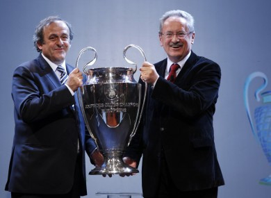 UEFA President Michel Platini, left, hands over the UEFA Champions League trophy cup to Mayor of Munich Christian Ude