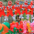 A Burmese girl stands behind balloon toys in Yangon. (AP Photo/Sakchai Lalit)