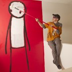 Street artist Stik poses in front of his work presented in a month solo exhibition entitled 'Walk', at the Imitate Modern Gallery in central London. (AP Photo/Joel Ryan)