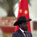 President Salva Kiir stands in front of a Chinese national flag while national anthems are played during a welcoming ceremony (AP Photo/Alexander F. Yuan)