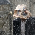 A man tries to shelter under a copy of the Financial Times newspaper as he runs through a heavy rain shower outside the Bank of England in London. (AP Photo/Matt Dunham)