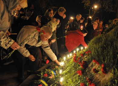 People lay flowers and light candles to honor the memory of the victims of the Chernobyl disaster in Kiev, Ukraine