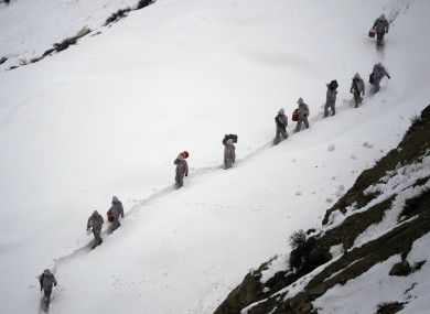 File photo of Pakistani soldiers bringing suppliers up the a mountain in February. 130 soldiers are thought to have been trapped by today's avalanche.