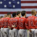 With a giant US flag across the left field wall, Los Angeles Angels pause for a moment of silence prior to facing the Boston Red Sox in a baseball game in Boston, Monday, May 2, 2011. (AP Photo/Charles Krupa)