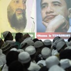 Members of hardline group Islam Defenders Front (FPI) gather by portraits of Osama Bin Laden and Barack Obama projected on a screen at their headquarters in Jakarta, Indonesia, Wednesday, May 4, 2011. (AP Photo/Irwin Fedriansyah)