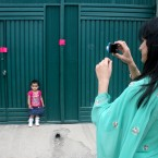 A Pakistani woman photographs her daughter at a gate of the compound where al-Qaeda leader Osama bin Laden was caught and killed in Abbottabad. (AP Photo/Aqeel Ahmed)