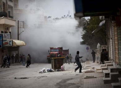 Syrian rebels amid smoke after a tank fired in Idlib, 11 March 2012.