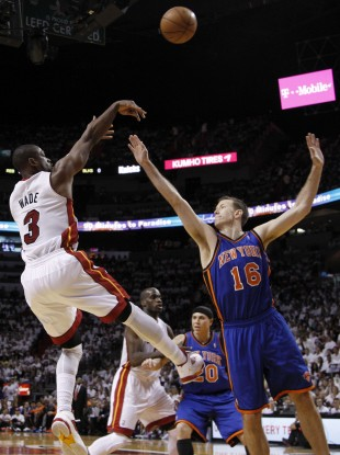 Miami Heat's Dwyane Wade (3) shoots past New York Knicks' Steve Novak (16) in the first half.