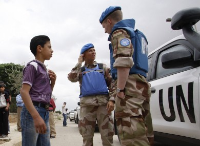 File photo: UN observers speak to a Syrian boy in Hama, 3 May 2012
