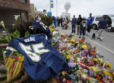 A San Diego Chargers #55 jersey sits in the foreground as fans look over a memorial set up in the driveway of former NFL star Junior Seau's home.