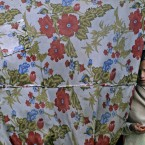An Afghan refugee girl, looks on while standing the doorway of her home in a slum area on the outskirts of Islamabad, Pakistan, Monday, May 7, 2012. (AP Photo/Muhammed Muheisen)
