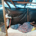 A woman lies in bed with her daughter inside a shack in a area occupied by Members of the Brazil's Landless Movement (MST) in Embu das Artes, outskirt of Sao Paulo, Brazil, Monday, May 7, 2012. (AP Photo/Andre Penner)
