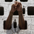 A prisoner rests his arms in the wall of his cell during a Mass for prisoners in the courtyard of La Esperanza penal center in San Salvador, El Salvador, Monday, May 7, 2012. The prisoners asked for Monsignor Fabio Colindres to hold a Mass for them at the prison. (AP Photo/Luis Romero)