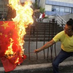 A protester burns a Chinese flag outside the Chinese consulate in suburban Makati, south of Manila, Philippines on Monday April 30, 2012. The Philippines and China are in a standoff over Scarborough Shoal which began early April after the Philippine navy accused Chinese boats of illegally fishing in the area. The Philippines says the shoal lies within its exclusive economic zone.(AP Photo/Aaron Favila)