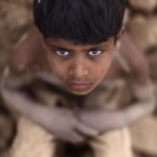 Pakistani Jaafar Sakhawat, 8, who works in a brick factory, looks up while taking a break, sitting on a pile of damaged bricks, on the outskirts of Islamabad, Pakistan, Wednesday, May 9, 2012. (AP Photo/Muhammed Muheisen)