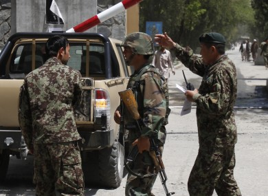 Afghan National Army soldiers secure the gate of the military hospital after Arsala Rahmani, a former Taliban official turned Afghan peace negotiator, was killed by an unknown attacker.