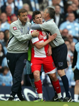QPR's Joey Barton is escorted from the pitch.