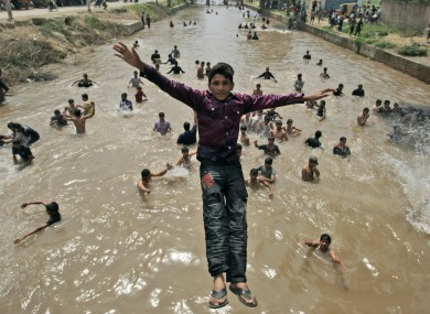 A young boy jumps into the water as he and his friends escape the heat in a canal, Lahore, Pakistan.
