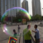 A kite vendor haggles with a customer near a bubble outside a park in Beijing, China. (AP Photo/Ng Han Guan)