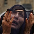 A Kashmiri Muslim woman prays as a priest (unseen) displays a relic believed to be a hair from the beard of the Prophet Mohammad, during special prayers on the death anniversary of Abu Bakr Siddiq, the first Caliph of Islam at Hazratbal Shrine on the outskirts of Srinagar, India. (AP Photo/Mukhtar Khan)