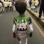 A Yemeni boy with the Syrian revolutionary flag painted on his body and Arabic which reads