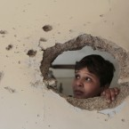A Lebanese boy looks through a hole made by shrapnel that hit his house, after the Lebanese army deployed at Syria street which divides the Sunni and Alawite areas, in the northern port city of Tripoli, Lebanon. (AP Photo/Hussein Malla)