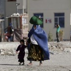 An Afghan woman carries her belongings on her head walks with a child in Kabul, Afghanistan, Thursday, May 17, 2012. Afghanistan, which was shattered by decades of war is suffering from severe poverty. (AP Photo/Rahmat Gul)