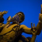 An anti-Nato protestor flashes peace signs during a protest march in Chicago. (AP Photo/John Minchillo)