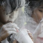 A Filipino girl blows powder out of a plastic cup using a straw during a game as part of celebrations of the feast day of Saint Rita de Cascia in suburban Paranaque, south of Manila, Philippines. (AP Photo/Aaron Favila)