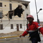 A civil protection volunteer walks past the damaged town hall building in St. Agostino, Italy, Sunday, May 20, 2012. (AP Photo/Luca Bruno)