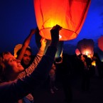 Young people launch paper lanterns into the air just outside Moscow, Russia. (AP Photo/Dasha Klimasheva)