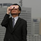A business man watches the eclipse at a waterfront park in Yokohama, near Tokyo (AP Photo/Shuji Kajiyama)