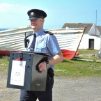 Garda Eugene Organ carrying a ballot box to the polling station for voting on the fiscal treaty referendum on Tory Island off the coast of Donegal (Photo: Artur Widak/PA Wire)