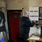 Barry Edgar Pilcher puts up a polling station sign in his living room in Inishfree Island today (AP Photo/Peter Morrison)