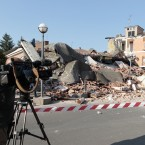 A cameraman films a collapsed building in Cavezzo, Italy (AP Photo/Gregorio Borgia)