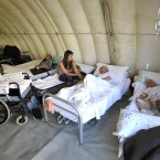 People rest in an Italian civil protection emergency tent set up in the earthquake hit town of Medolla, northern Italy (AP Photo/Marco Vasini)