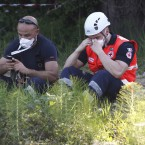 A firefighter and policemen rest as they look for three workers who are reportedly missing at the Haemotronic factory in Medolla, northern Italy (AP Photo/Luca Bruno)