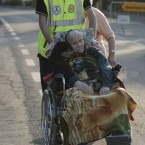 A woman is pushed on a wheelchair by an Italian Civil Protection volunteer in Cavezzo, Italy(AP Photo/Gregorio Borgia)