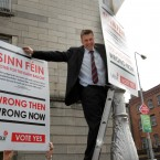 It all works out well in the end: Hannigan hangs two posters on a lampost opposite the Sinn Fein shop in Dublin. Photo: Sam Boal / Photocall Ireland