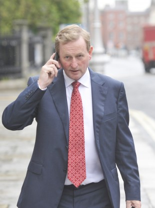 Taoiseach Enda Kenny doing a bit of mobile working of his own as he arrives at government buildings yesterday.