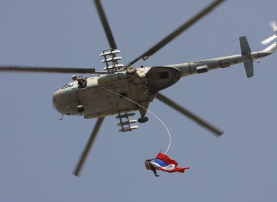 A Syrian regime supporter dangles from a helicopter as he waves Russian and Chinese flags