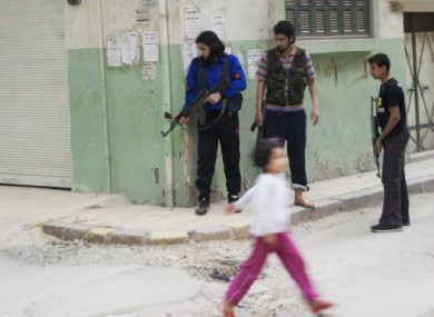 A young girl walks by rebel fighters in the Khaldiyeh neighbourhood of Homs.