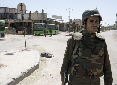 A Syrian government soldier stands guard in Damascus last month