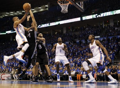 Oklahoma City Thunder point guard Russell Westbrook, left, shoots against San Antonio Spurs guard Danny Green (4) and guard Tony Parker (9).