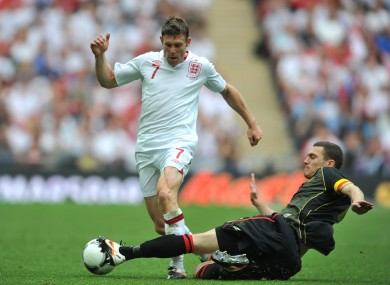 Belgium's Thomas Vermaelen (right) slides in to challenge England's James Milner.