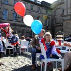 Amelia Paris 5, (centre) with mother Lisa (left) swinging sister Elizabeth, at a street party on the Royal Mile, Edinburgh, during the Diamond Jubilee celebrations.