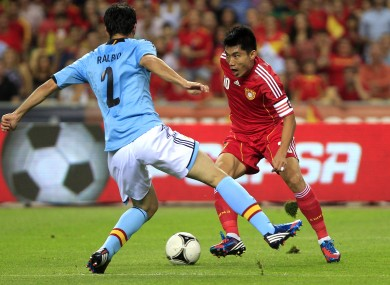Spain's Raul Albiol, left and China's Zheng Zhi-Cap, right, fight for the ball.
