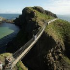Torchbearer Denis Broderick holds the Olympic Flame on the Carrick-a-Rede rope bridge during Day 17 of the London 2012 Olympic Torch Relay. Image: Ben Birchall/PA