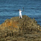 Torchbearer Peter Jack holds the Olympic Flame aloft on the Giant's Causeway.